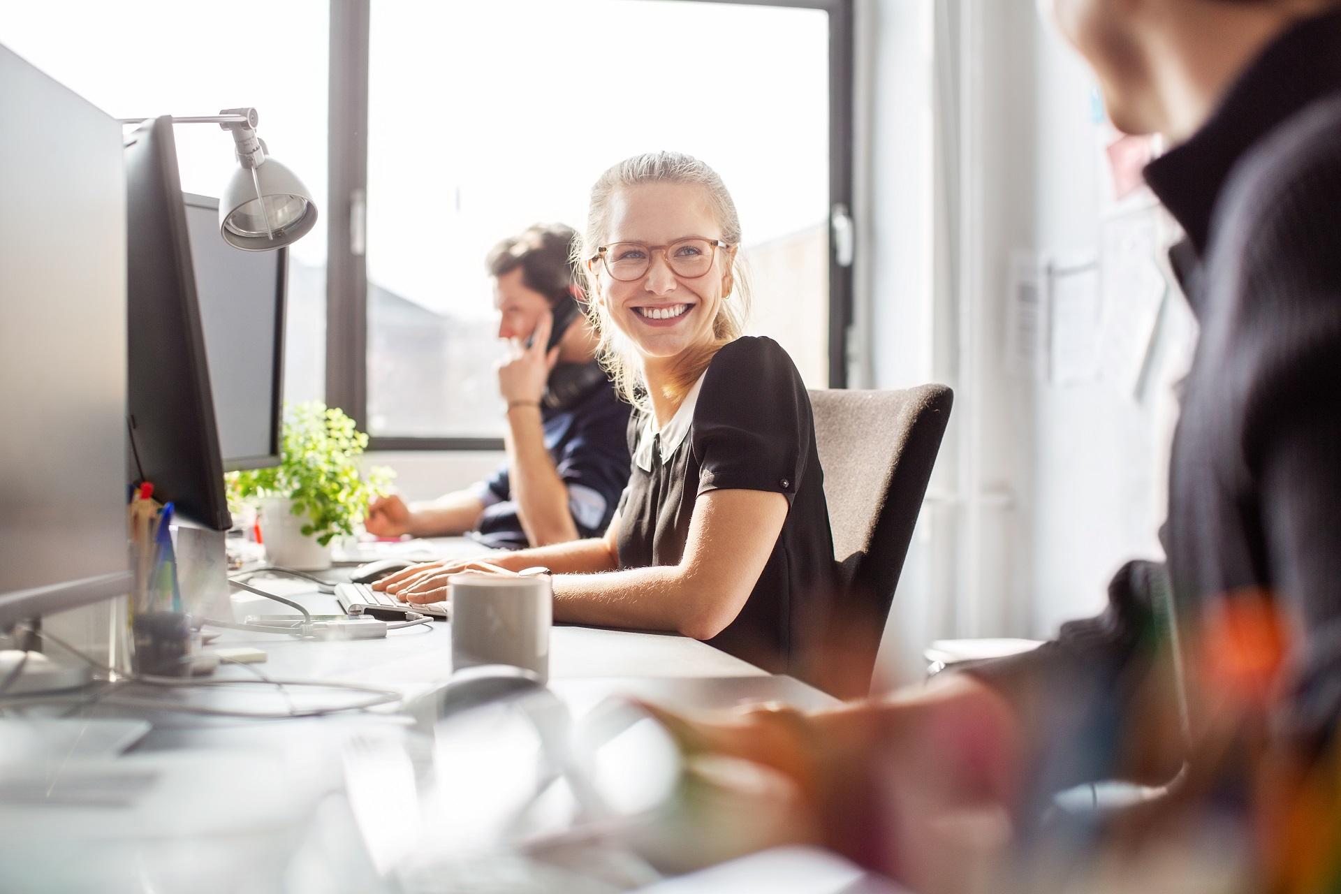 Frau arbeitet mit ihren Kollegen im Büro - Die Bätza Köster GmbH